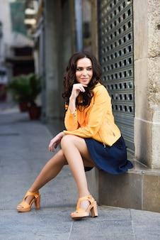 都市背景で微笑む若いブルネット女性。