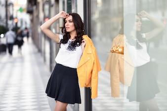 都市の背景に立っている若いブルネットの女性。