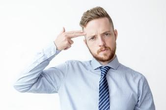 Молодой бизнесмен, стреляющий в себя пальцами