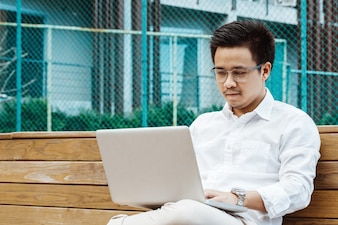 Young businessman working on laptop at garden
