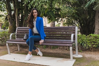 Young businesswoman sitting on a bench and looking down