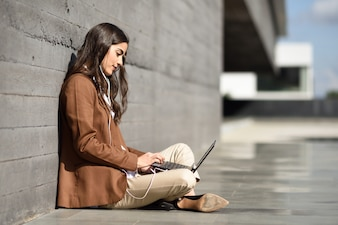 Young businesswoman sitting on floor looking at her laptop computer. Beautiful woman wearing formal wear using earphones.