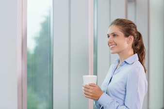 Young Businesswoman with Cup at Window