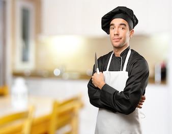 若いシェフ、調理器具を使用して疑いのジェスチャー