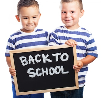 Young children smiling with a blackboard with the message  back to school