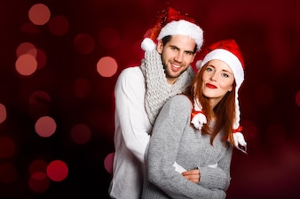Young couple dressed with winter clothes and santa hat on a red background with bokeh