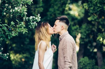 Young couple kissing in green