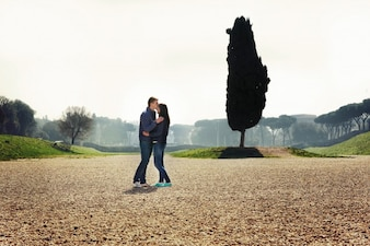 Young couple stands in green park in Rome