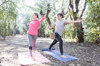 Young couple stretching arms and legs during a yoga class