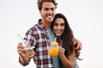 Young couple with drink at the beach