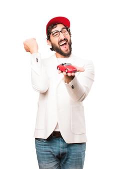 赤い車のおもちゃで若いクレイジーなビジネスマン