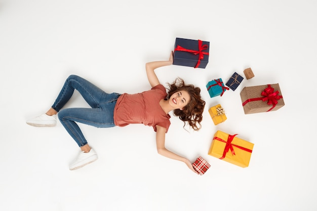 Young curly woman lying among gift boxes