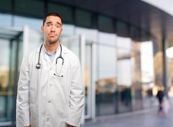 悲しみのジェスチャーをしている若い医者