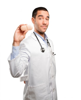 Young doctor holding a pill