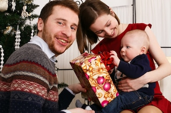 Young family sits with their little son before Christmas tree