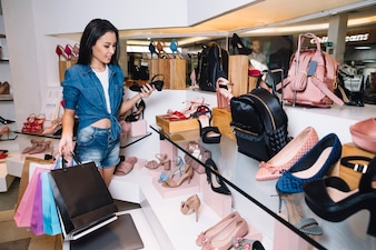 Young female consumer choosing shoes