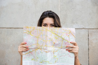 Young female traveler peeking out from behind map