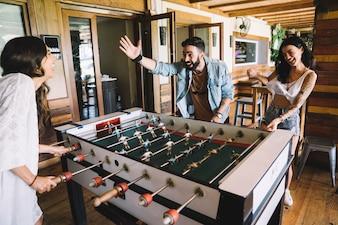 Молодые друзья играют в настольный футбол