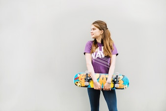 Young girl holds skateboard while looking to the right