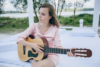 Young girl in a pink dress playing a guitar