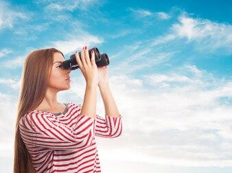 Young girl looking asidethrough binoculars