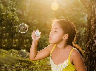Young girl making a soap bubble