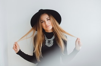 Young girl posing with a hat and grabbing her hair