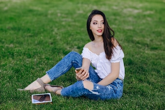 Young girl sitting in a park with a tablet in the grass and a mobile in the hand