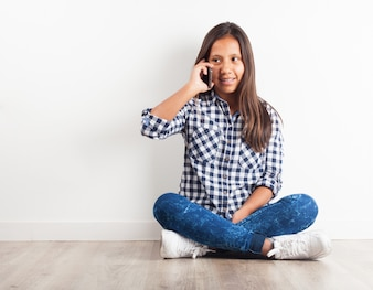 Young girl sitting on the floor talking on the phone