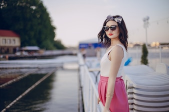 Young girl with pink skirt and sunglasses posing on a railing