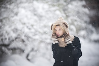 Young girl wrapped in the snow with unfocused background