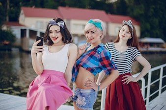 Young girls posing on a white railing and one looking at her mobile phone