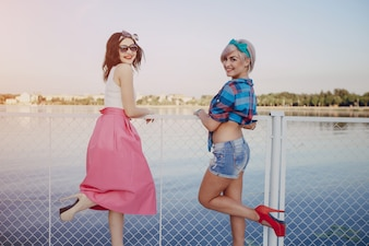 Young girls posing with one leg lifted on a white fence