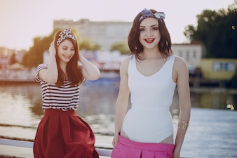 Young girls posing with sea and buildings in background