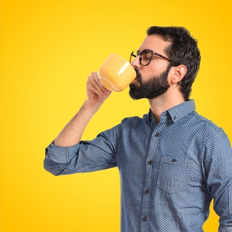 Young hipster man drinking coffee over white background on colorful background
