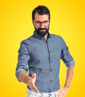 Young hipster man making a deal on colorful background
