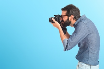 Young hipster man photographing over white background on colorful background