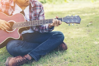 Young hipster man practiced guitar in the park,happy and enjoy p