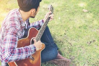 若いヒップスターの男性は、公園でギターを練習幸せとpを楽しみます