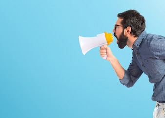 Young hipster man shouting by megaphone on colorful background