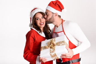 Young man giving a christmas gift to his woman with a kiss