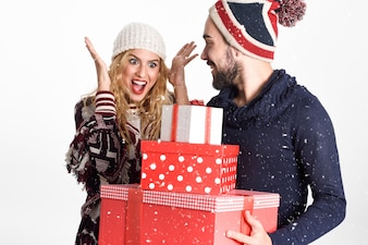 Young man giving many christmas gifts to his woman, dresses with winter clothes on white background