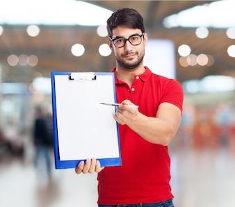 若い男は白紙でクリップボードを保持します