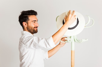 Young man leaving hat on clothes hanger