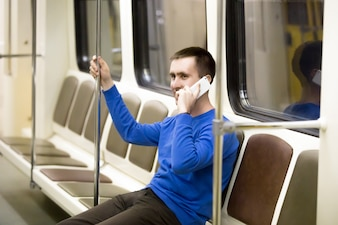 Young man on mobile phone in subway train