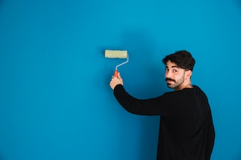Young man painting blue wall