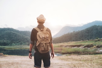 Young Man Traveler with backpack relaxing outdoor. Summer vacations and Lifestyle hiking concept.