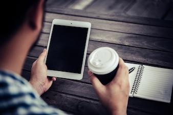 若い男は飲みながらデジタルタブレットを使用しています。家庭の庭に座ってコーヒー、朝はリラックスします。