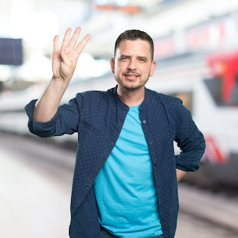 Young man wearing a blue outfit. Doing four number gesture.