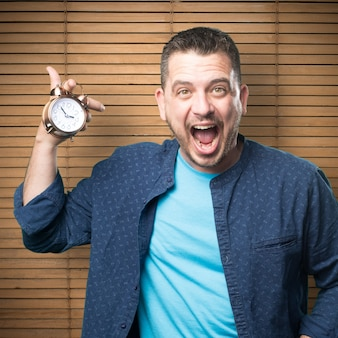 Young man wearing a blue outfit. Holding a clock. He is yelling.